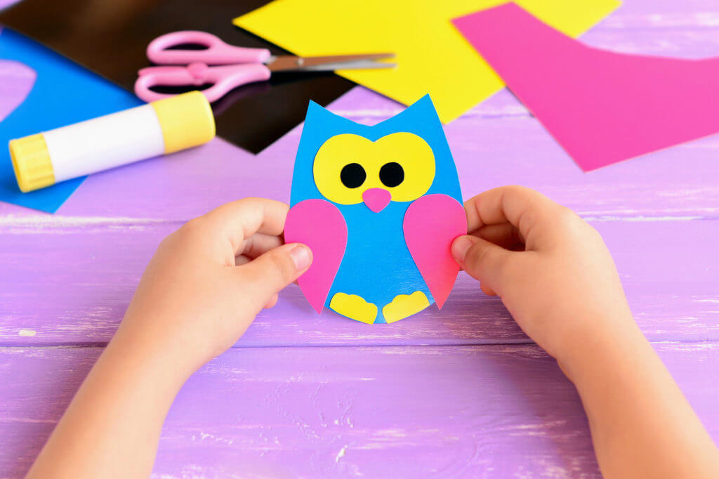 Small child holds craft activity from book subscription for kids
