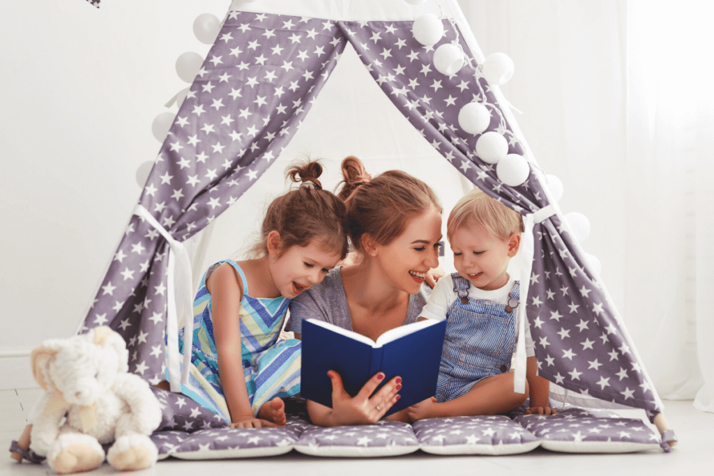 How to Get Your Child to Love Reading - mom sitting in a tent reading to her kids